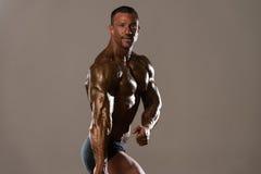 Muscular Man Flexing Muscles Stock Photo