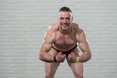 Muscular Man Flexing Muscles On White Bricks Background Royalty Free Stock Photography