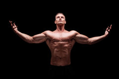 Muscular man gesturing with hands and looking up. On black background Royalty Free Stock Images