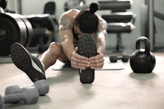 Muscular man in gym doing exercises. Stock Photography