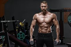 Muscular man in gym with dumbbells. Strong male naked torso abs, workout.  stock photo