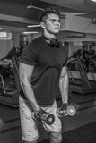 Muscular man in the gym. Performing heavy exercise. Work on your body. Photos for magazines, posters and websites Stock Photo