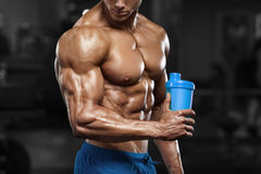 Muscular man in gym with shaker, shaped abdominal. Strong male naked torso abs, working out Royalty Free Stock Photo