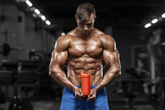 Muscular man in gym with shaker, shaped abdominal. Strong male naked torso abs, working out.  royalty free stock photo