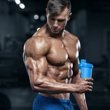 Muscular man in gym with shaker, shaped abdominal. Strong male torso abs, working out.  Stock Photo