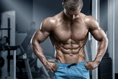 Muscular man in gym, sixpack abs. Strong male nacked torso, working out Royalty Free Stock Photos