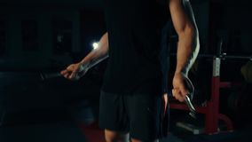 Muscular man in the gym, training legs jumping with a rope with the concept of bar selection of fitness and bodybuilding