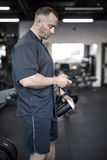 Muscular man has pause in gym Stock Photography