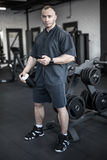 Muscular man has pause in gym. Powerful man with big muscles stands in the gym next to the dumbbell weights set. He holds a cup in the right hand and a cellphone Royalty Free Stock Photos