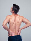 Muscular man having pain in back. Over gray background Stock Photo