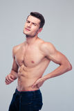 Muscular man having pain in back. Over gray background. Looking at camera Royalty Free Stock Images