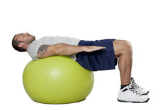 Muscular man with healthy ball doing exercises Royalty Free Stock Photography