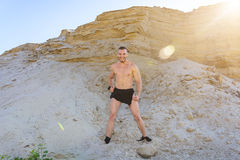 Muscular man in the hip primal bandage posing against a background of sand. stock images