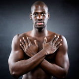 Muscular man with his arms protected his body. Royalty Free Stock Image