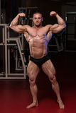 Muscular Man Is Hitting Rear Double Bicep Pose Stock Images