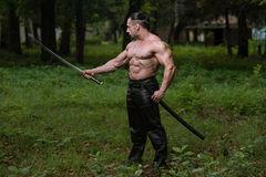 Muscular Man Holding Ancient Sword Stock Photo
