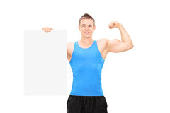 Muscular man holding a banner and showing bicep Royalty Free Stock Image