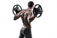 Muscular man holding a barbell on his shoulders, rear view. stock images