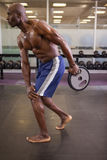 Muscular man holding barbell weight in gym Stock Photography