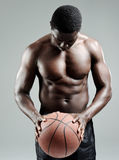 Muscular man holding a basketball Royalty Free Stock Photography