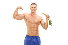 Muscular man holding a carrot and showing bicep Royalty Free Stock Photos