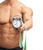 Muscular man holding clock and measuring tape. Cropped view of a muscular young man holding clock and measuring tape over white background. It is high time for Royalty Free Stock Photo