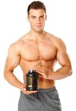 Muscular man holding container. Muscular man holding black container of training supplements Royalty Free Stock Image