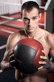 Muscular man holding fitness ball in front of chest Stock Photography