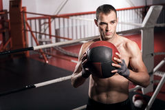 Muscular man holding fitness ball in front of chest Royalty Free Stock Image