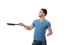 Muscular man holding frying pan. Stock Photography