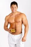 Muscular man holding a hamburger Stock Image