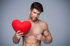 Muscular man holding heart shape Stock Photos