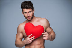 Muscular man holding heart shape Royalty Free Stock Photos
