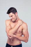 Muscular man holding his elbow in pain Royalty Free Stock Photos