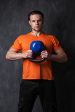 Muscular man holding a kettlebell in hands royalty free stock photo
