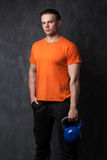 Muscular man holding a kettlebell in hands royalty free stock photos