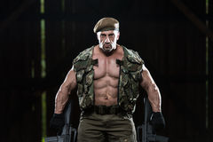 Muscular Man Holding Machine Guns Royalty Free Stock Photos