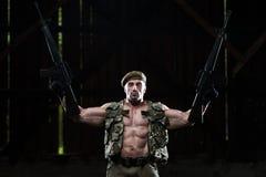 Muscular Man Holding Machine Guns Stock Photos
