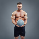 Muscular man holding a medicine fitness ball Stock Photography