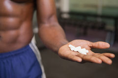 Muscular man holding vitamin pills in hand Royalty Free Stock Photography