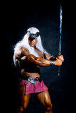 Muscular man in an image of a barbarian with a raised sword. Against a dark background Stock Image