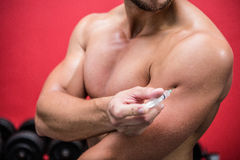 Muscular man injecting steroids. In crossfit gym royalty free stock photos