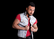 Muscular man with jeans gilet (vest) and headphones around his neck Royalty Free Stock Photos