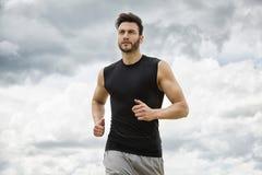 Muscular man jogging outdoors, dramatic sky backdrop stock photography