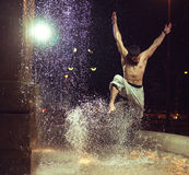 Muscular man jumping in fountain Royalty Free Stock Photography