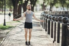 Muscular man jumping using skipping rope outdoors. Street workout, fitness, sport, morning training, outdoor activity and lifestyle concept. Young fit muscular Royalty Free Stock Images