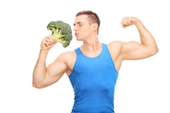 Muscular man kissing a huge piece of broccoli. Isolated on white background Stock Photos