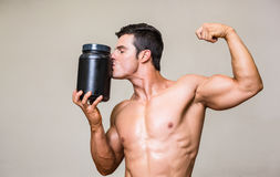 Muscular man kissing nutritional supplement. Shirtless muscular man kissing nutritional supplement over white background Stock Images