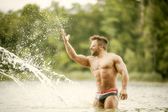 Muscular man lake Stock Images