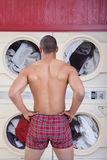 Muscular Man In Laundromat Stock Images